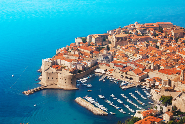 The clear aquamarine waters, ancient fortifications and distinctive red-tiled roofs of the picturesque city of Dubrovnik