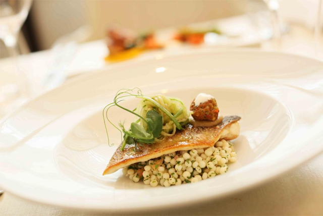 Steamed Cornish sea bass served with tomato couscous, caramelised shallot puree, salt fish puffs and xiyar salati